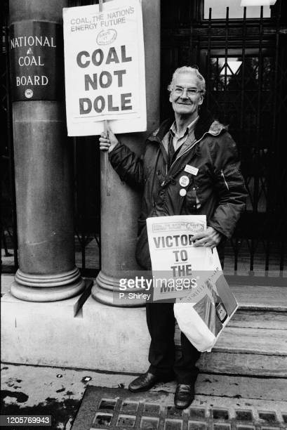 Protester holding placards saying 'Coal Not Dole'and 'Victory To The Miners' on the miners' strike picket outside the headquarters of the National...