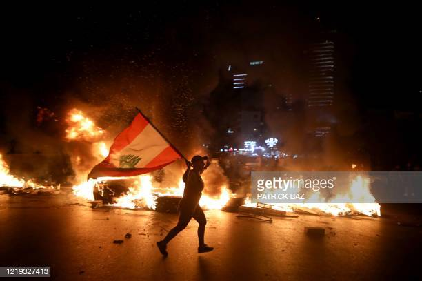 Protester holding the Lebanese flag runs as protesters block the Jounieh Tripoli highway with flaming tires set aflame during a demonstration against...