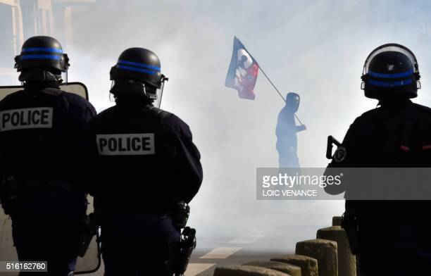 TOPSHOT A protester holding the National Confederation of Labour union flag faces antiriot police during a demonstration against the government's...