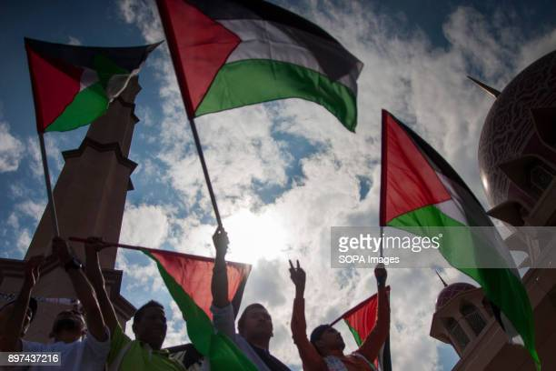 Protester holding the Palestinian flag to show some support at the solidarity rally Hundred of Malaysian people had gathered at Putrajaya Mosque to...