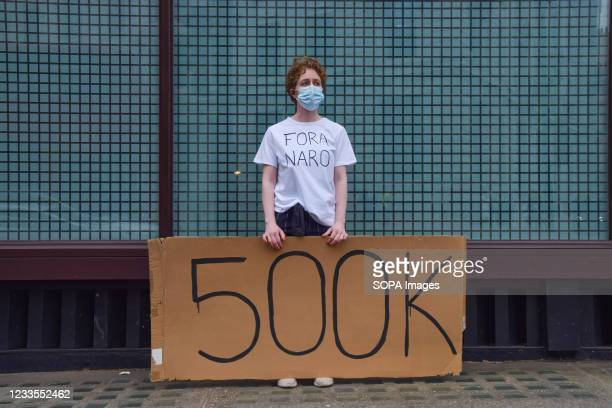 Protester holds a '500k' placard in reference to the number of lives lost to COVID-19 in Brazil during the demonstration against president Jair...