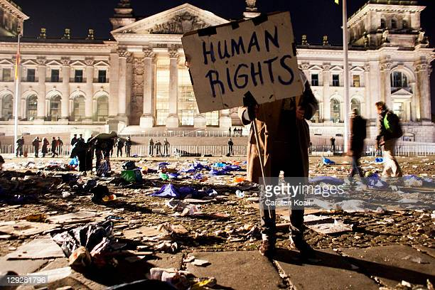 A protester holds a banner after a sitin demonstrating against the influence of bankers and financiers in front of the Reichstag building on October...