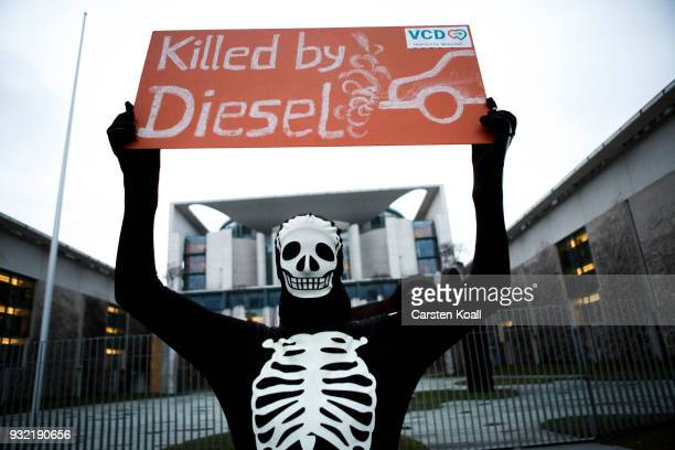 A protester holds a banner during a protest by cyclists against the ongoing diesel affair in front of the Chancellory as the new German Cabinet held...