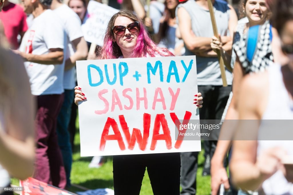 A protester holds a banner reading 'DUP + MAY SASHAY AWAY' at a rally calling for the resignation of British Prime Minister Theresa May and against forming a coalition government with the Democratic Unionist Party in London, United Kingdom on June 10, 2017.