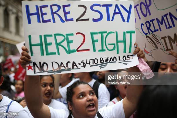 A protester holds a banner reading 'Here To Stay Here To Fight No DACA = 470 Billion Dollars Lost' during a rally against US President Donald J...