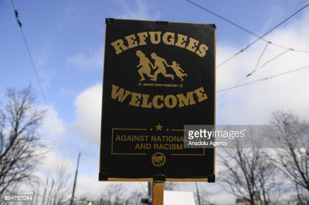 A protester holds a banner reading 'Refugees Welcome' during a demonstration against the new Austrian government during the swearingin day at...
