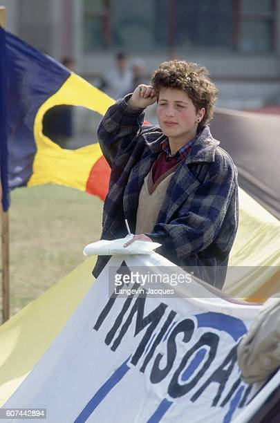 A protester holds a banner reading 'TIMISOARA' the name of the city where protests against the government began in 1989 A Romanian flag flies behind...
