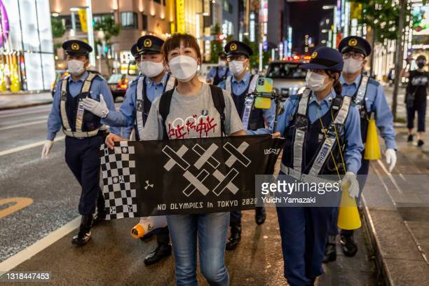 Protester holds a banner saying 'No Olympic in Tokyo 2020' in Ginza area during a protest against the Tokyo Olympics on May 17, 2021 in Tokyo, Japan....