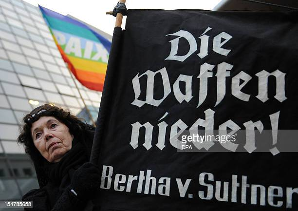 A protester holds a banner that quotes Nobel Prize winner Bertha von Suttner Lay Down Your Arms to demonstrate against German arms export in front of...