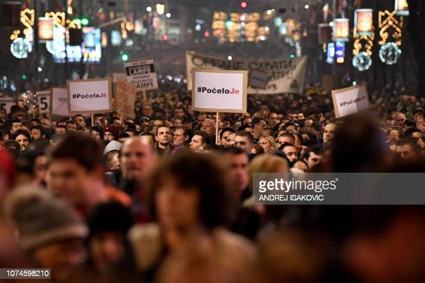 A protester holds a banner that reads It started as thousands of people many blowing whistles take part in a protest against the Serbian president in...