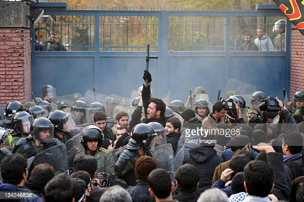 Protester holds a baton in the air as police in riot gear hold a large number of demonstrators attempting to storm the British Embassy in front of...