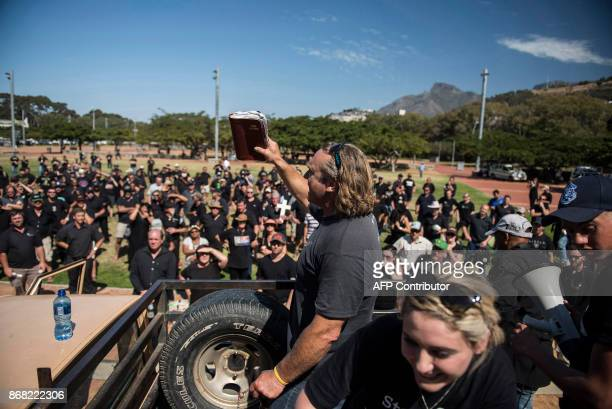 A protester holds a bible as he speaks to South African farmers farm workers gathered at a demonstration at the Green Point stadium to protest...