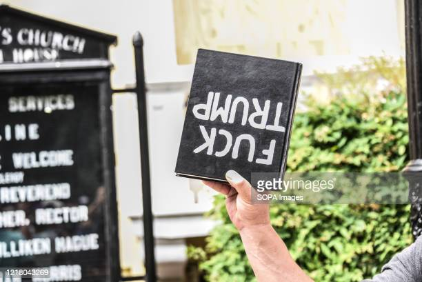 A protester holds a bible upside down to mimic President Donald Trump who stood in front of the St John's Church last week holding a bible upside...