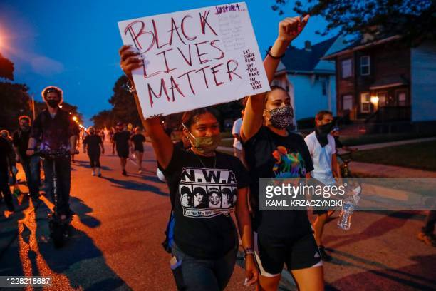 A protester holds a Black Lives Matter sign during a demonstration against the shooting of Jacob Blake in Kenosha Wisconsin on August 26 2020 Outrage...