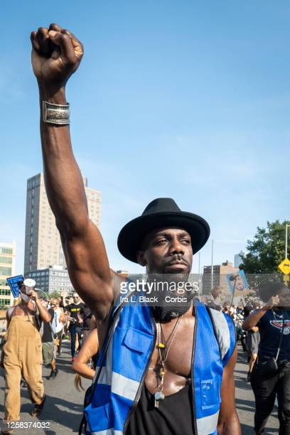 A protester holds a black power raised fist above their head as they take part in thousands that marched out from Cadman Plaza in Brooklyn NY and...