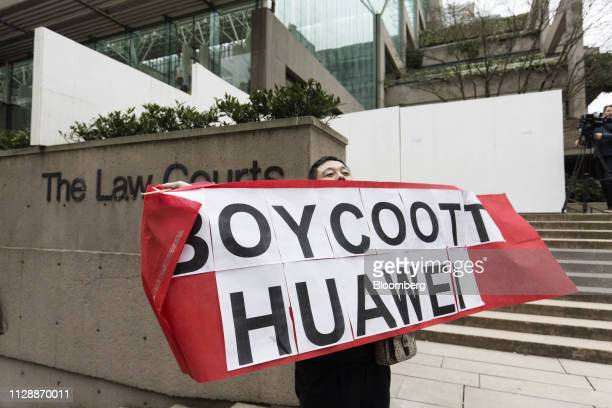 A protester holds a Boycott Huawei sign in front of the Supreme Court following a hearing of Huawei Technologies Co Chief Financial Officer Meng...