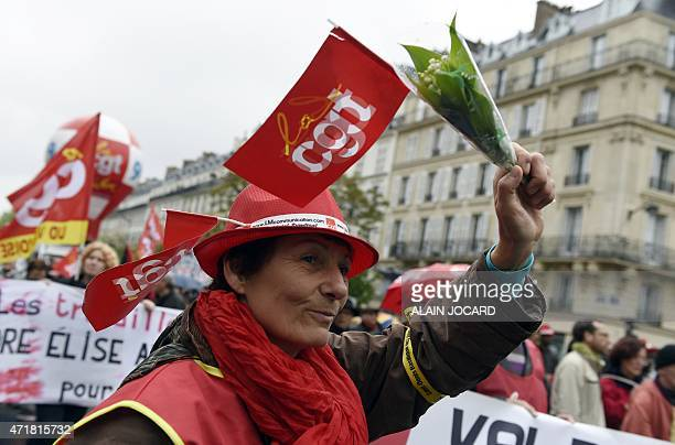 A protester holds a bunch of Lily of the valley as she attends a demonstration organized by unions marking May Day on May 1 2015 in Paris Tens of...