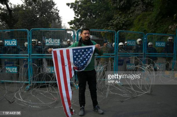 A protester holds a burned US flag during a demonstration near the US consulate following a US airstrike that killed top Iranian commander Qasem...