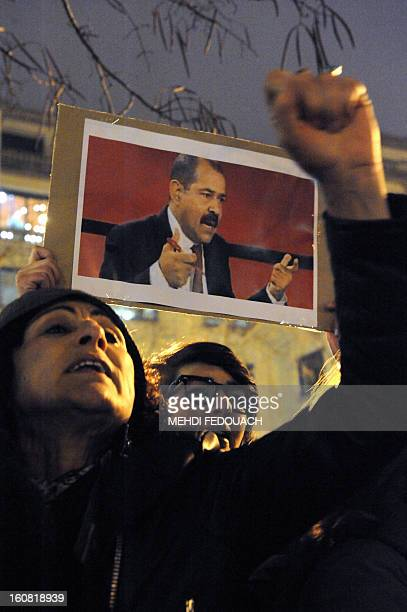 A protester holds a cardboard bearing a portrait of Tunisian opposition leader Chokri Belaid during a demonstration on February 6 2013 held outside...