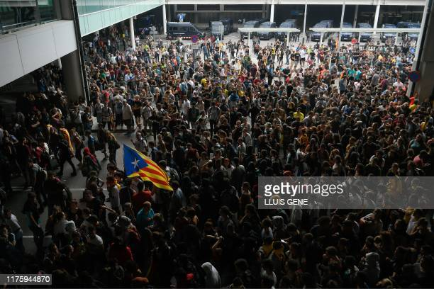 TOPSHOT A protester holds a Catalan proindependence Estelada flag surrounded by other protesters at El Prat airport in Barcelona on October 14 2019...
