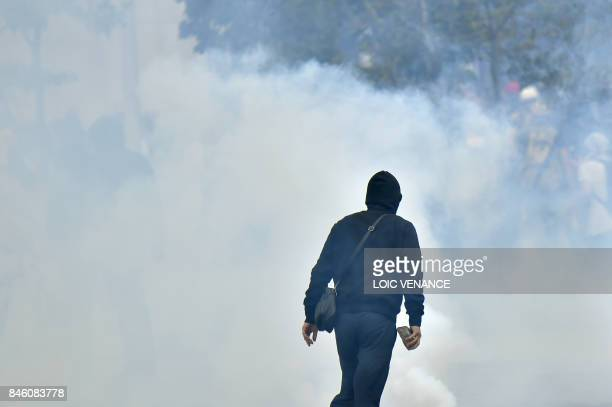 Protester holds a cobblestone during clashes within a protest called by several French unions against the labour law reform, on September 12, 2017 in...