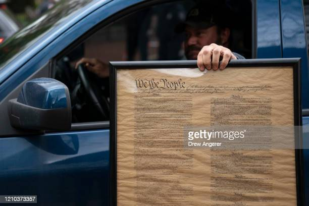 A protester holds a copy of the Constitution as he drives in protest with the group Reopen Maryland near the State House to call on the state to lift...