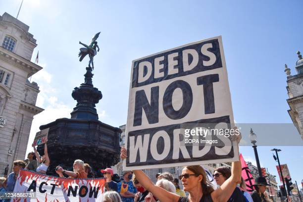 Protester holds a 'Deeds Not Words' placard during the demonstration in Piccadilly Circus. Extinction Rebellion protesters marched through central...