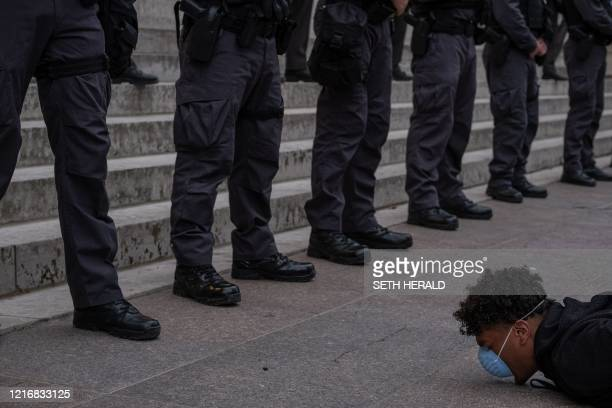 TOPSHOT A protester holds a diein in front of a row of police officers during a peaceful protest over the death of George Floyd at the State Capital...