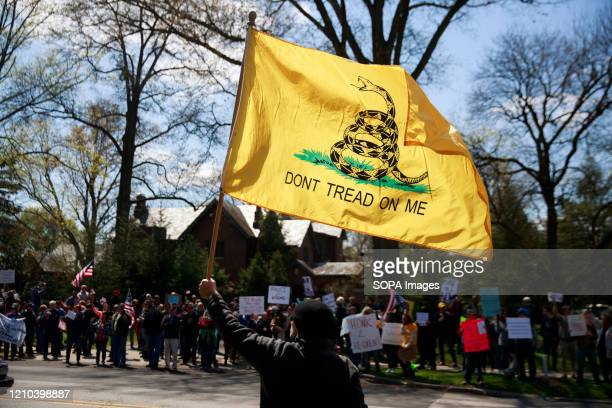 Protester holds a Don't Tread on Me flag during the demonstration. Protesters gather outside Indiana Governor Eric Holcomb's mansion in the 4700...