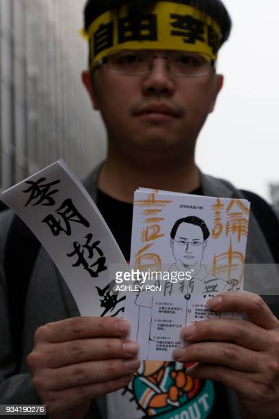 A protester holds a drawing of Taiwanese activist Lee Mingche during a demonstration in Taipei on March 19 2018 Taiwanese human rights activist Lee...