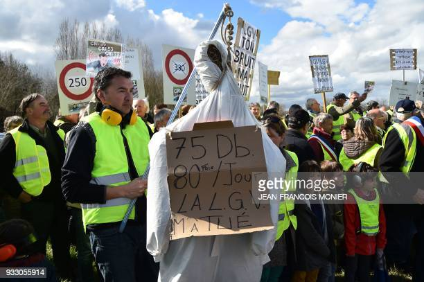 A protester holds a fake hanged man on which reads '75 DB 85 times a day LGV killed me' during a protest against the Ligne A Grande Vitesse between...