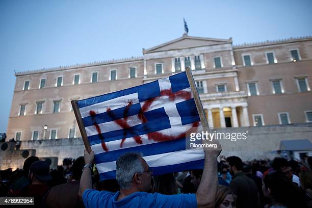 A protester holds a flag during an antiausterity demonstration in support of the Greek government in Syntagma Square in Athens Greece on Monday June...