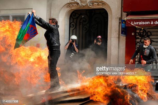 A protester holds a flag of the Romani people as he stands on burning planks on the sidelines of the annual May Day rally in Paris on May 1 2019...