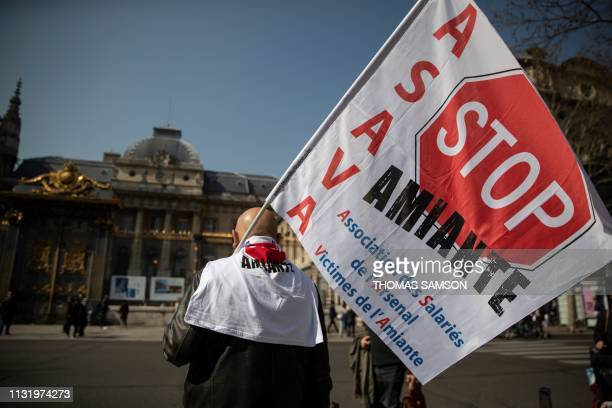 """Protester holds a flag reading """"Stop asbestos"""" during a gathering near the courthouse in Paris, on March 22 while the Court of Cassation examines an..."""