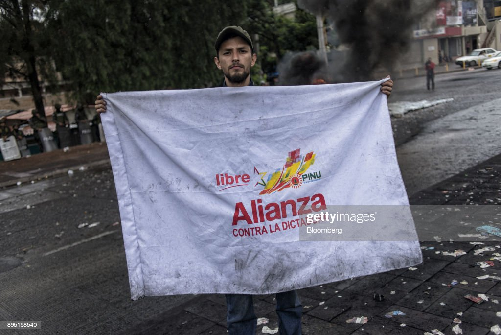 A protester holds a flag representing the opposition alliance during protests against the presidential election of Juan Orlando Hernandez in Tegucigalpa, Honduras, on Monday, Dec. 18, 2017. Honduran electoral authorities declared incumbent Hernandez the winner of the Nov. 26 presidential vote after three weeks in which the nation slid into chaos as ballots were counted and recounted. Photographer: Juan Carlos/Bloomberg via Getty Images