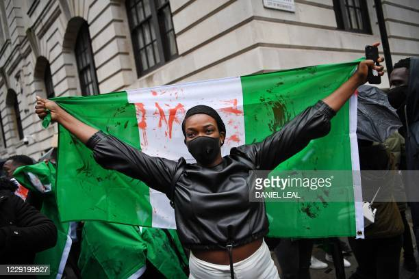 Protester holds a flag stained with fake blood during a demonstration outside the Nigerian High Commission against police brutality in Lagos in...
