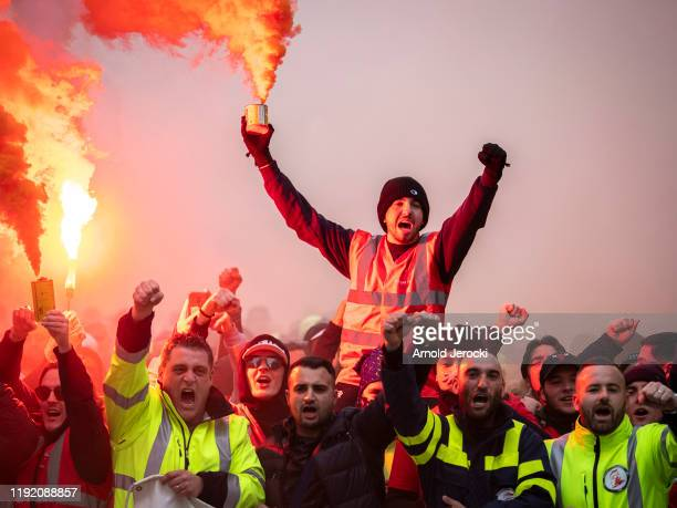 A protester holds a flare as public and private workers demonstrate and shout slogans during a mass strike against pension reforms on December 05...