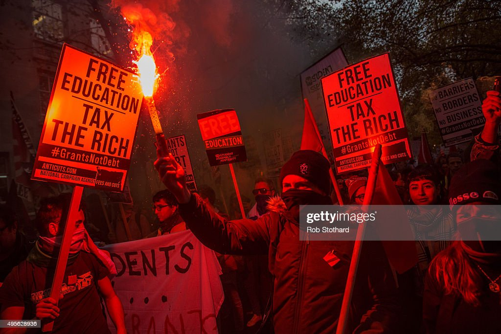 A protester holds a flare during a protest against education cuts and tuition fees outside the University of London on November 4, 2015 in London, England. University students from across the country are marching on the streets of London to protest against cuts to free education. After a rally outside what was the University of London Union, the march will take in Parliament Square, Millbank - occupied by student protesters five years ago - and end in front of the Department for Business, Innovation and Skills (the department responsible for universities).