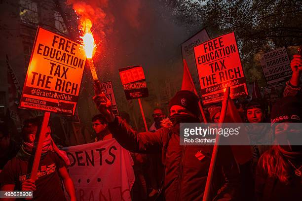 A protester holds a flare during a protest against education cuts and tuition fees outside the University of London on November 4 2015 in London...