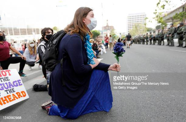 A protester holds a flower while protesting the killing of George Floyd outside of San Jose City Hall in downtown San Jose Calif on Sunday May 31 2020