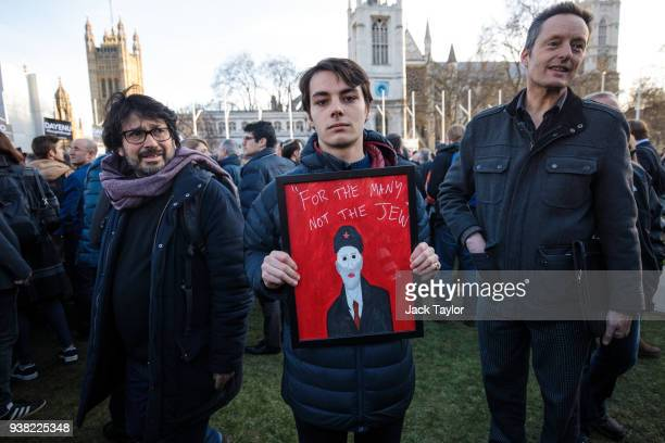 A protester holds a framed image of Labour Leader Jeremy Corbyn and the words For The Many Not The Jew during a demonstration in Parliament Square...