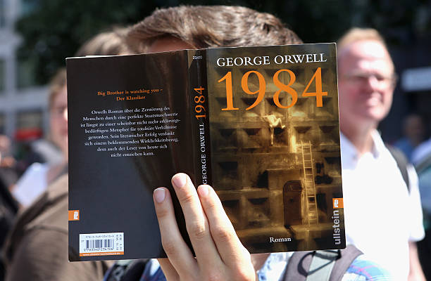 Protester holds a German translation of George Orwell's book '1984' as he demonstrates for journalists' rights on August 1, 2015 in Berlin, Germany....