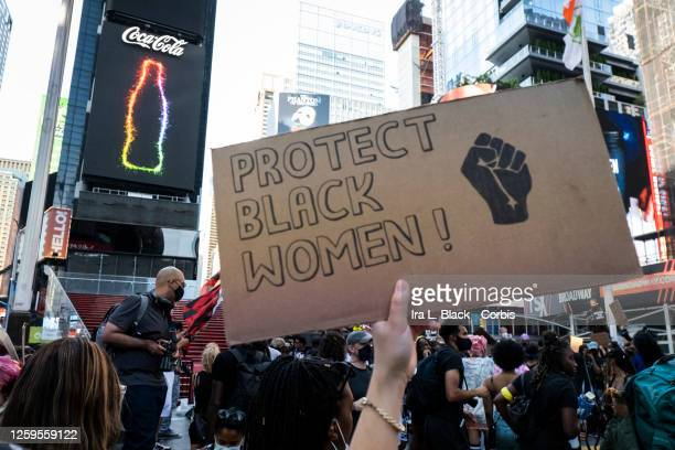 A protester holds a handmade sign that says Protect Black Women with the a black power fist on it and the CocaCola Jumbotron behind in Father Duffy...