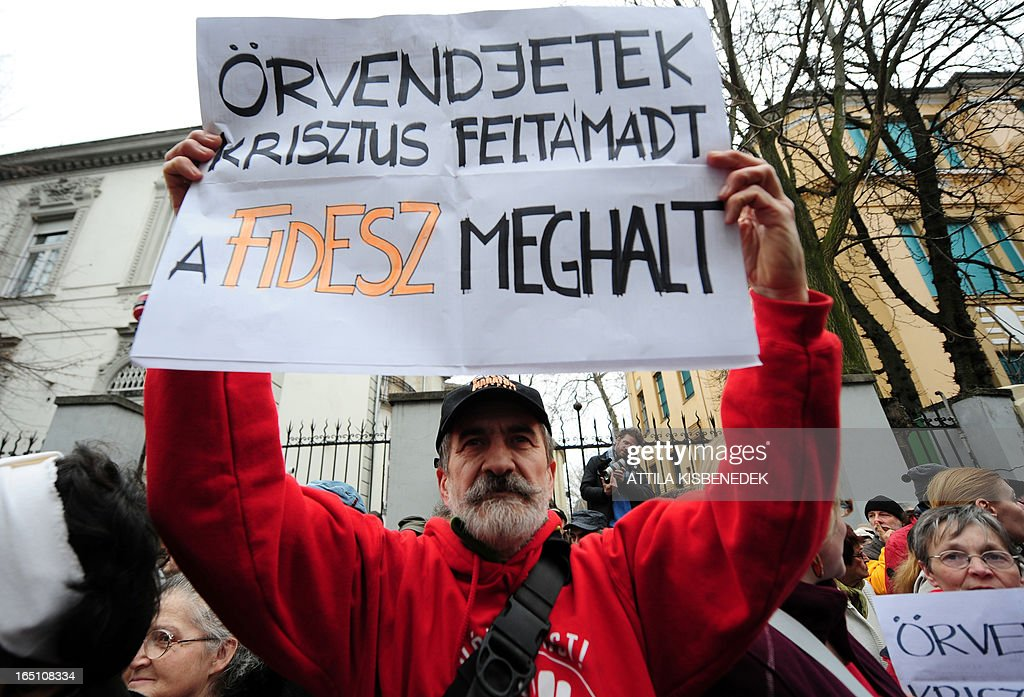 A protester holds a home-made banner with a text 'Rejoice, Jesus Christ is arised, the FIDESZ is dead', to protest against the new Hungarian Constitution during an anti-government demonstration in front of the headquarters of the governor FIDESZ in Budapest on March 30, 2013. The fourth modification of the basic law will be come into force on April 1.