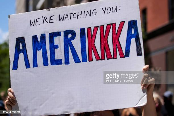 A protester holds a homemade sign that says We're Watching You Amerikka with the letters of the kkk in red during a protest with hundreds of people...