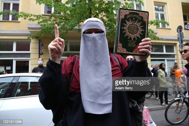 Protester holds a Koran while demonstrating against restrictions on public life designed to stem the spread of the coronavirus, or COVID-19, on April...