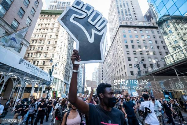 A protester holds a large black power raised fist through the streets of 5th Avenue in New York with hundreds of other protesters This was part of...