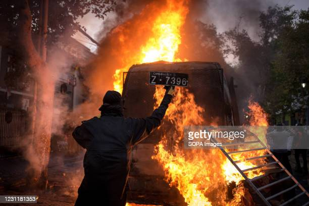 Protester holds a license plate of a burning police vehicle during the demonstration. Several protesters took to the streets to protest against...