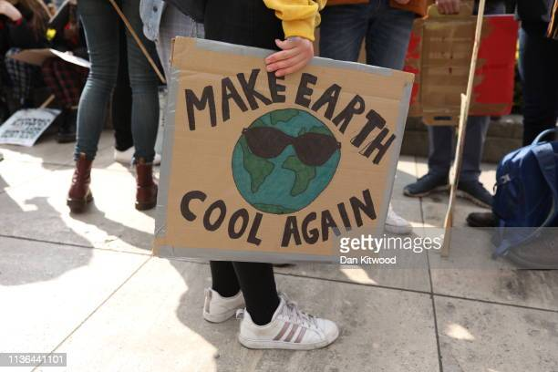 A protester holds a 'Make Earth Cool Again' sign at the YouthStrike4Climate student march on April 12 2019 in London United Kingdom Students are...