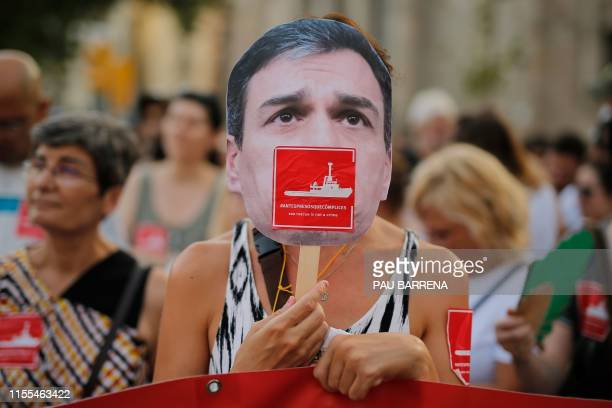 A protester holds a mask of Spanish Prime Minister Pedro Sanchez with a sticker reading Sea rescue is not a crime during a demonstration in Barcelona...
